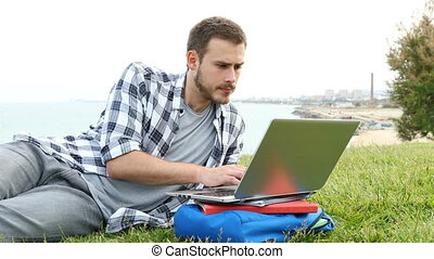 Serious student using a laptop on the grass