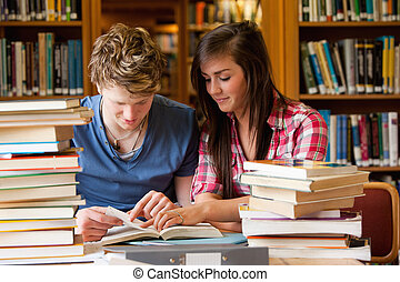 Serious students looking at a book in a library