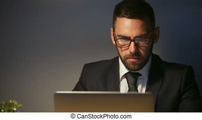 Serious successful businessman using laptop in home office, working late