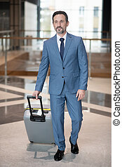 Serious successful businessman walking with luggage in the hotel