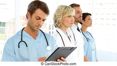 Serious surgeon writing on clipboard while staff are...