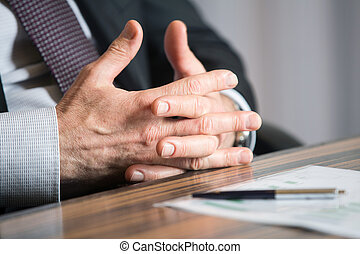 Man's hands holding a black pen in both arms in a thinking gesture during a meeting or negotiation