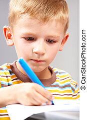 Serious task - Close-up of school boy drawing picture