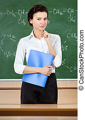 Serious teacher is near the blackboard