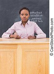 Serious teacher sitting at a desk in a classroom