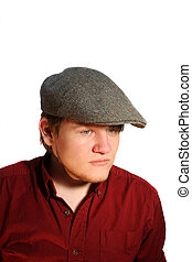 Head and shoulders shot of a serious teenage boy wearing a British wool flat cap, isolated on a white background.