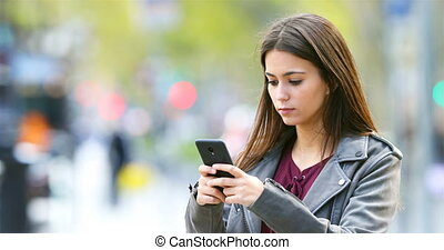 Serious teen texting on smart phone outdoors