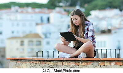 Serious teen using a tablet on vacation