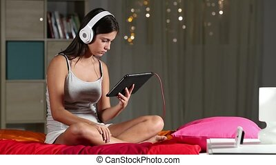 Serious teen watching tablet content sitting on a bed in the...