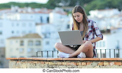 Serious teen writing on a laptop on vacation
