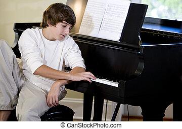 Serious teenage boy looking down at piano keys