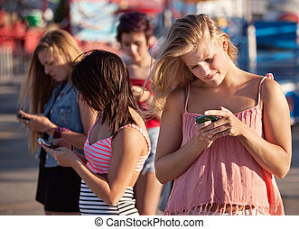 Serious Teenagers on Smartphones - Four female teenagers ...