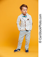 Serious thinking little boy child standing isolated