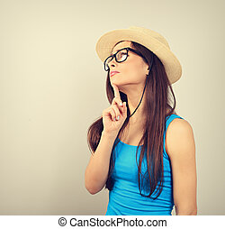 Serious thinking young woman looking in fashion glasses and straw hat on blue background