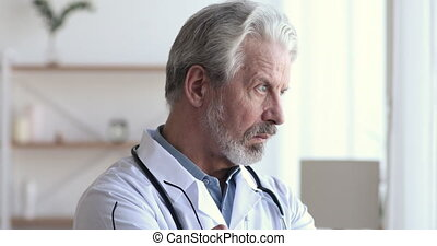 Serious thoughtful old doctor looking through window thinking of challenges
