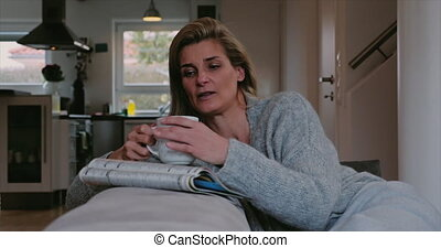 Serious thoughtful woman relaxing with coffee