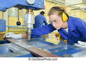 serious trainees focused on drilling metal piece with...