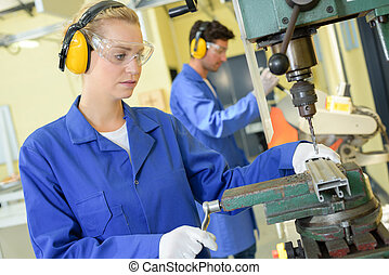serious trainees focused on drilling metal piece with professional machinery