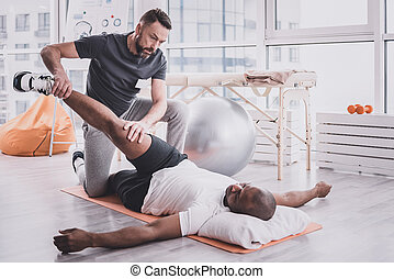 Serious trainer stretching leg of his patient