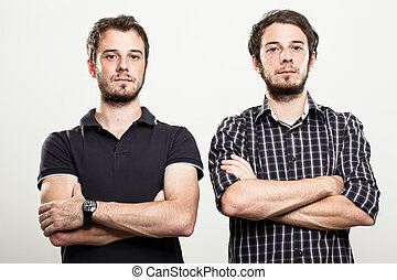 Serious Twins - Two Serious Twins with Arms Folded