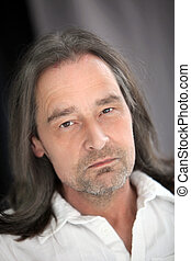 Serious unshaven man with long hair