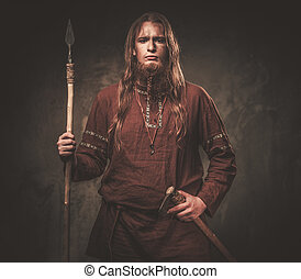 Serious viking with a spear in a traditional warrior...