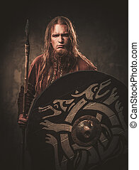Serious viking with a spear in a traditional warrior clothes...
