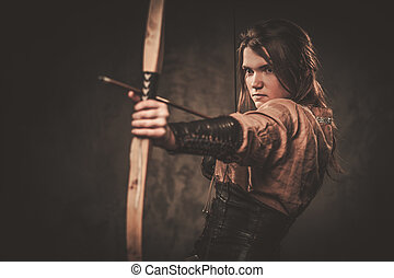 Serious viking woman with bow and arrow in a traditional...
