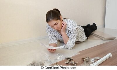 serious woman analyzes guidance note for assembling cabinet...