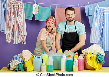 serious woman and man expressing negative emotion in the laundry room