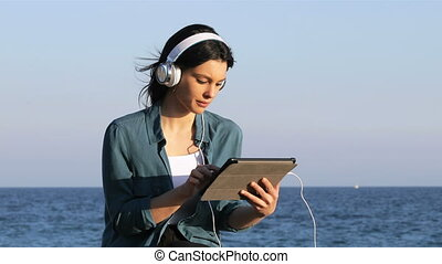 Serious woman browsing and listening tablet content sitting...