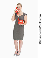 Serious woman calling with a retro phone