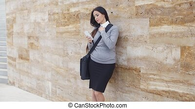 Serious woman checking email on phone outdoors
