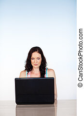 Serious woman focused on her laptop with copy-space