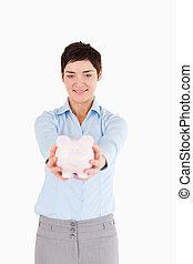 Serious woman holding a piggy bank