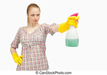Serious woman holding a spray bottle while looking away