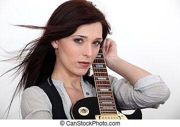 Serious woman hugging her guitar
