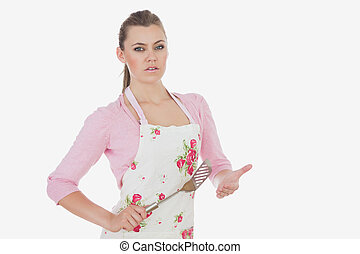Serious woman in apron holding spatula