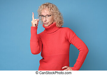 Serious woman in glasses pointing index finger up giving advice.