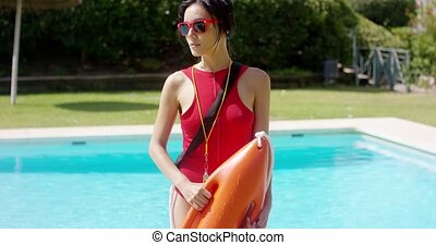 Serious woman in lifeguard uniform beside pool