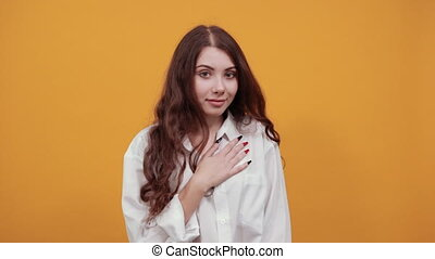 Serious young woman in fashion white shirt keeping hands on chest, showing victory gesture, looking at camera isolated on orange background in studio. People sincere emotions.