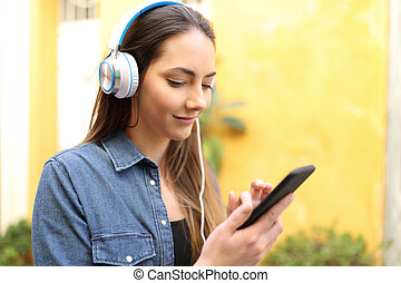 Serious woman listening to music using phone