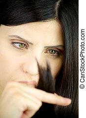 Serious woman looking damaged hair