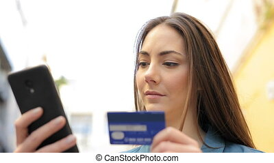 Serious woman paying with credit card online
