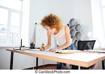 Serious woman photographer with curly red hair working in office