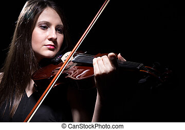 Serious woman playing on violin