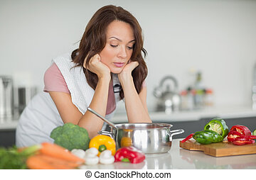 Serious woman preparing food in kitchen