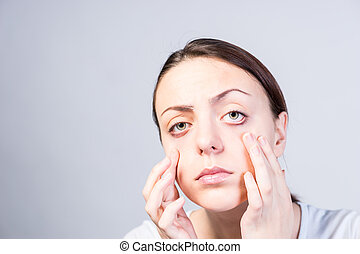 Serious Woman Pulling Down her Lower Eyelids - Serious Young...