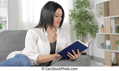 Serious woman reading a book sitting on a couch in the living room at home