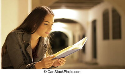 Serious woman reading a book in the night